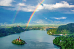Breathtaking panoramic view of Lake Bled from above with double rainbow on the sky