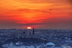 Breathtaking sunset over Lviv city, Ukraine. The aircraft takeoff over the horizon