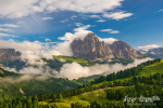 Magnificent view of Sassolungo massif and Gardena valley covered by white clouds, Dolomites, Italy